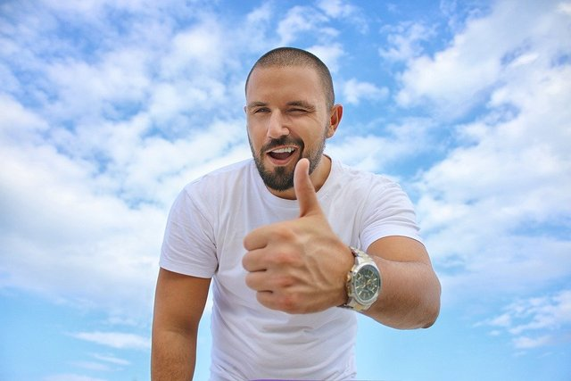 Young man blue sky thumbs up luxury watch success