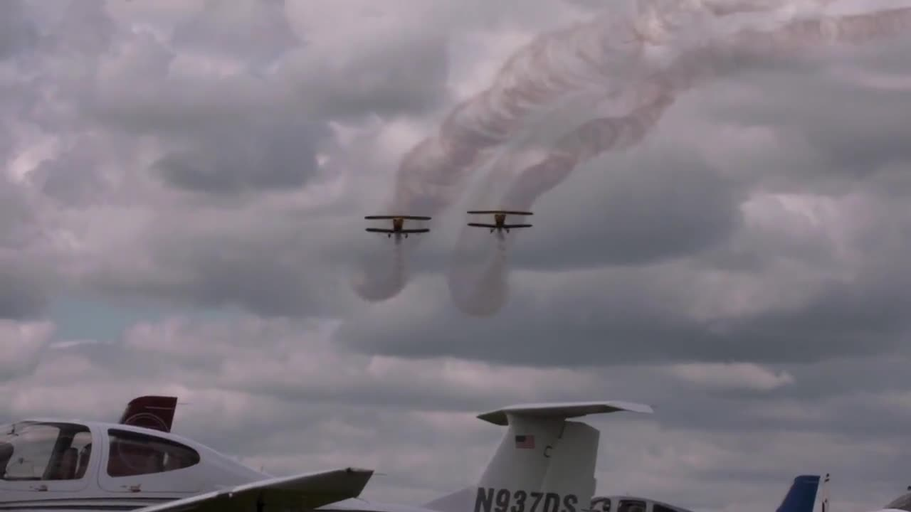 Air show exhibition of two yellow biplanes